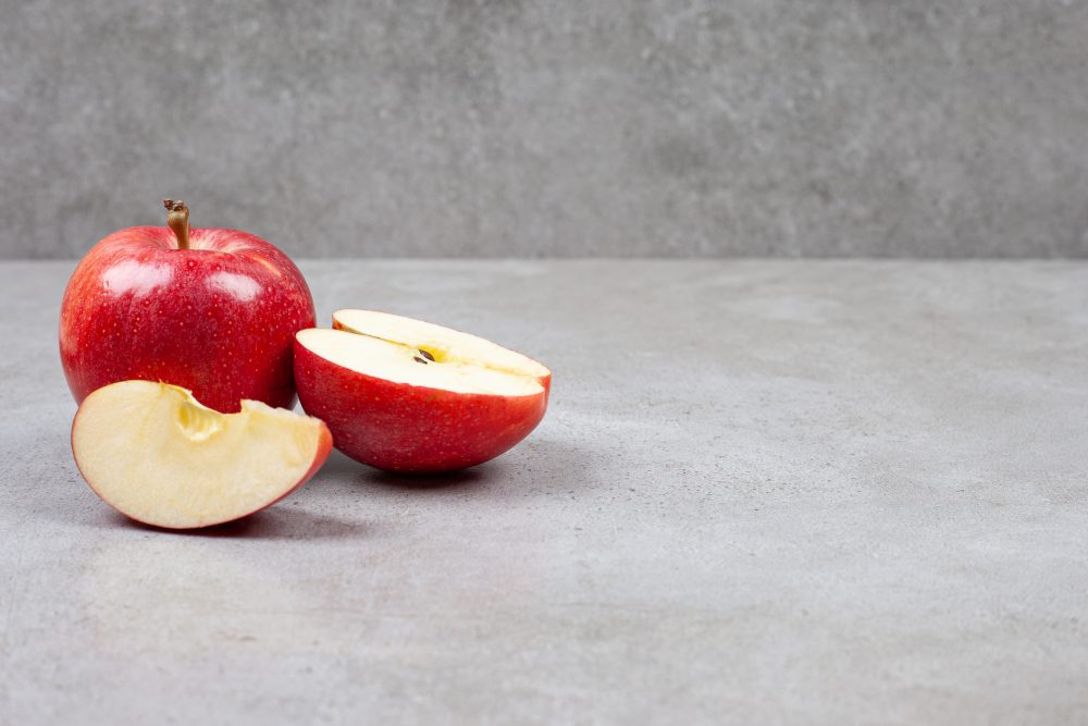Fresh organic apples. Whole or sliced red apples on grey background